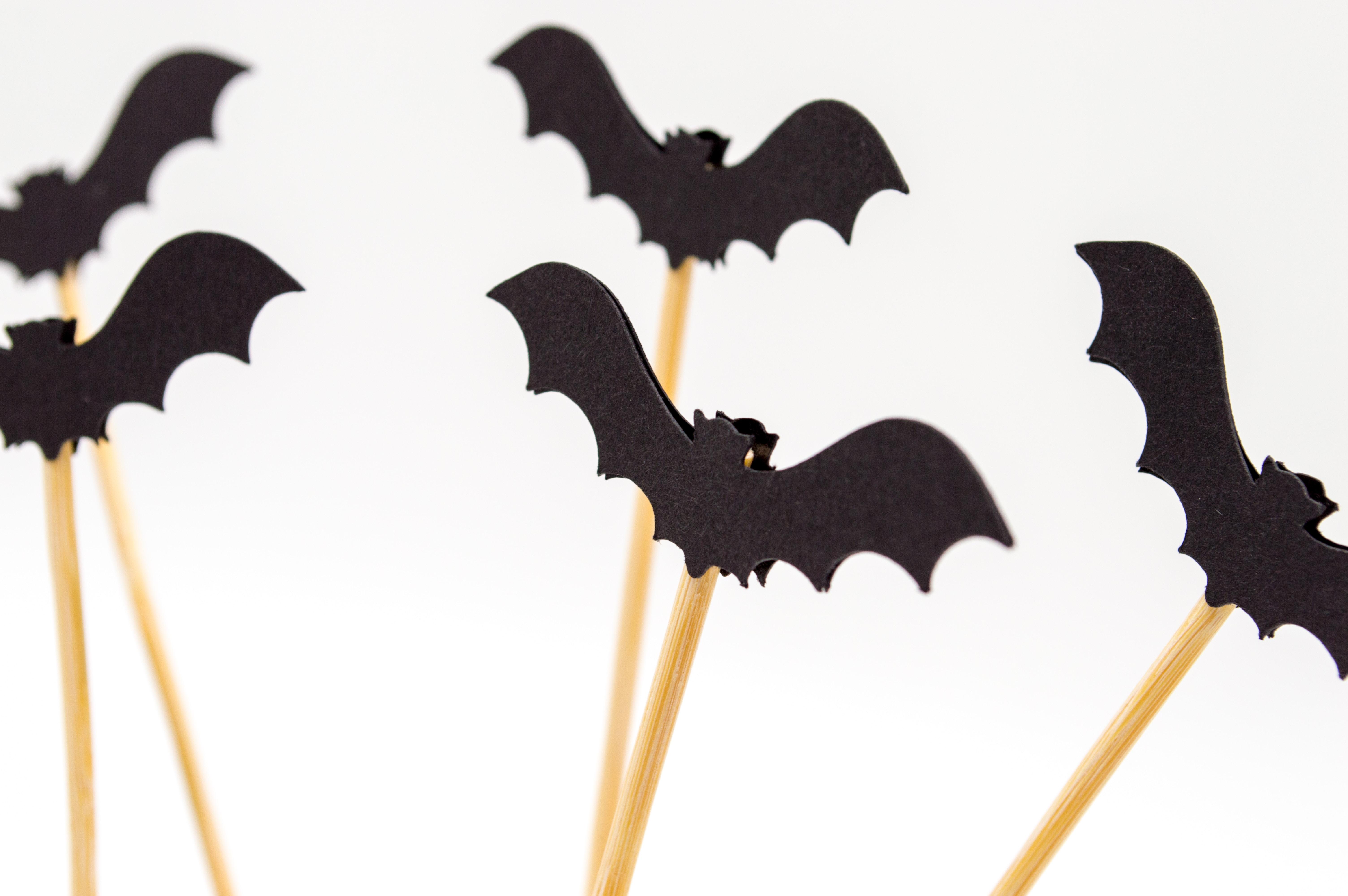 five black toy bats with sticks