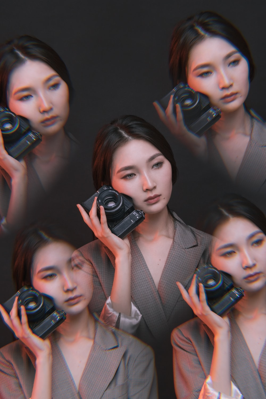 edited photo of woman holding black DSLR camera