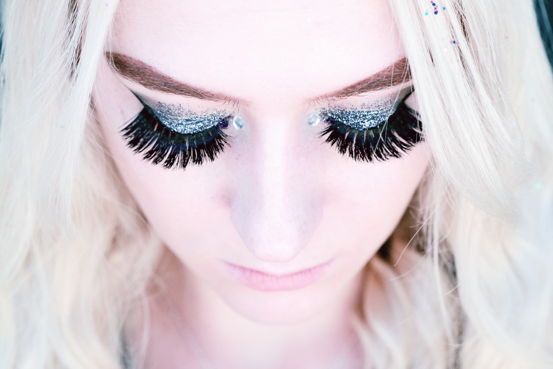 A close up portrait looking down on an 18 year old person wearing false eyelashes and glitter eye shadow.