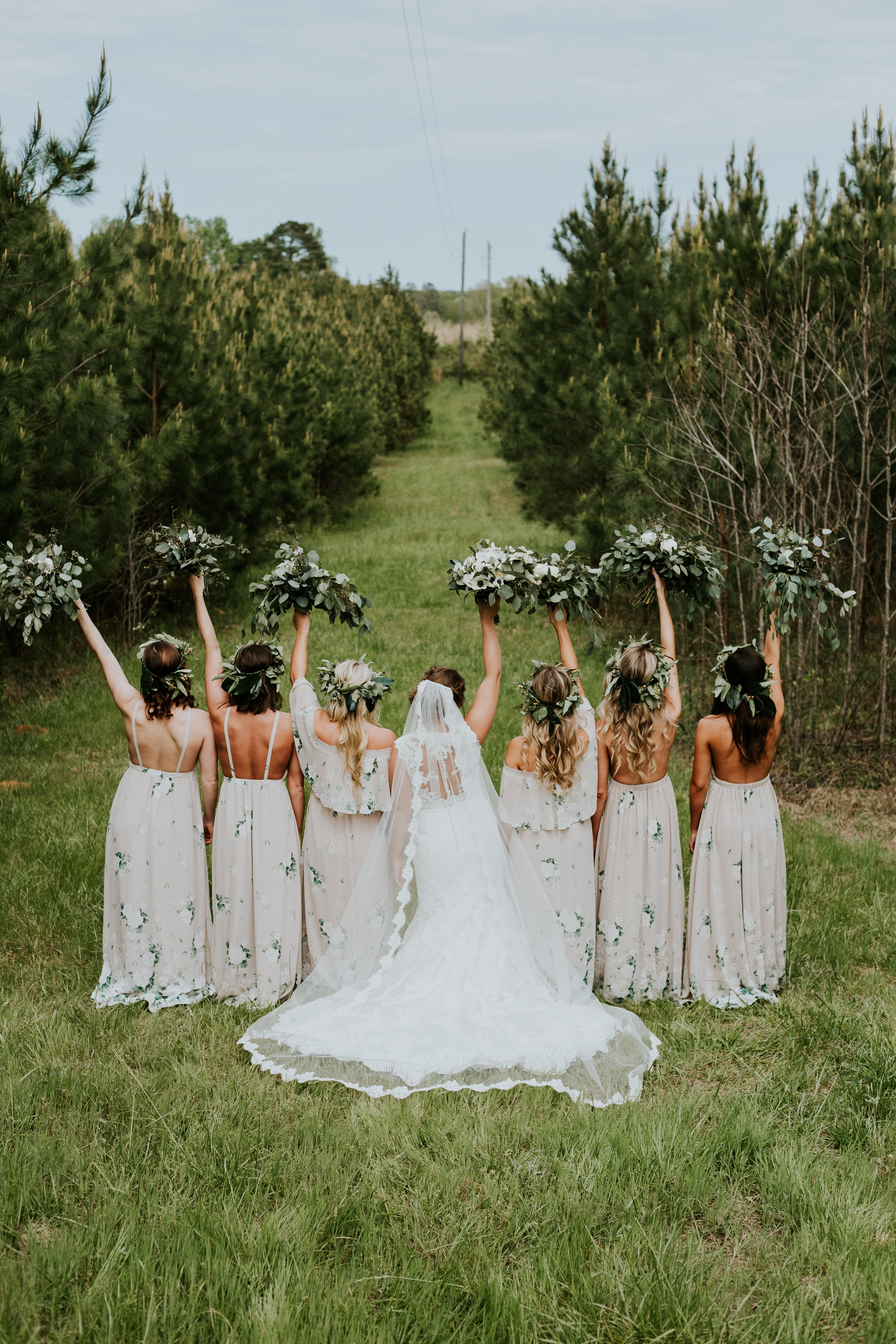 group of women holding high floral bouquets during daytime