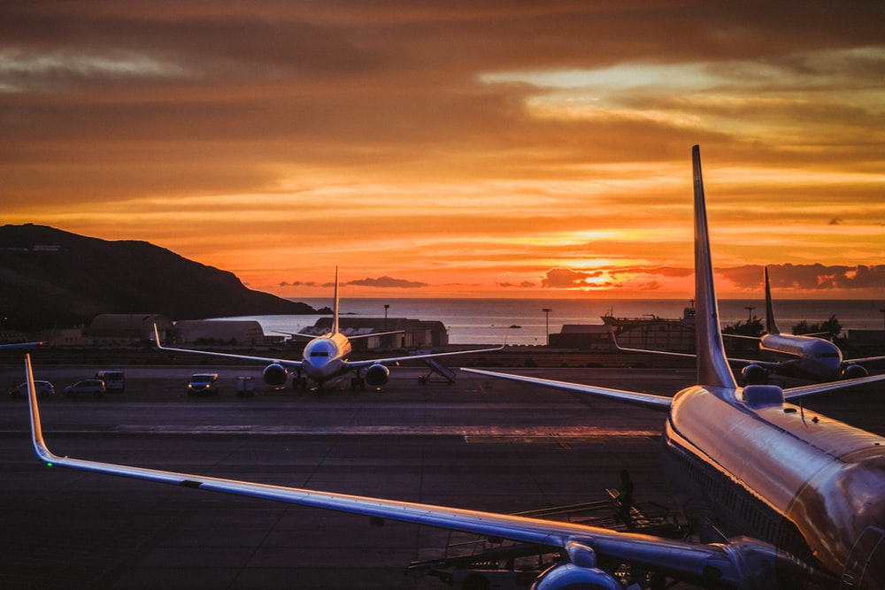 three airplane parked on road during golden hour