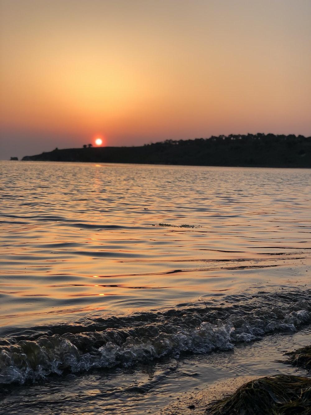 body of water near island at sunset