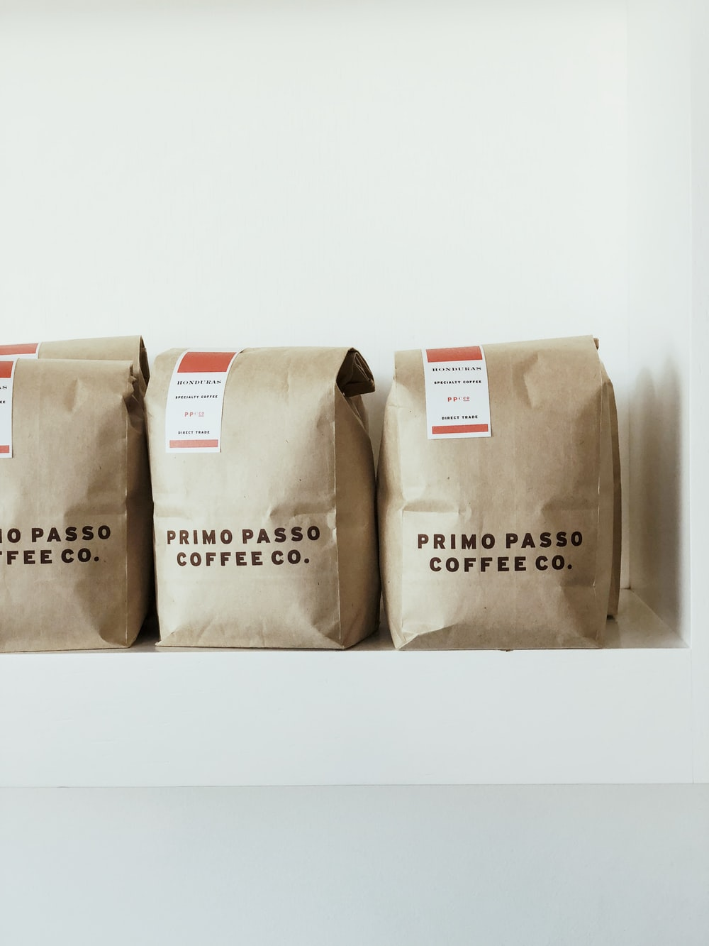 three brown Primo Passo Coffee co packs