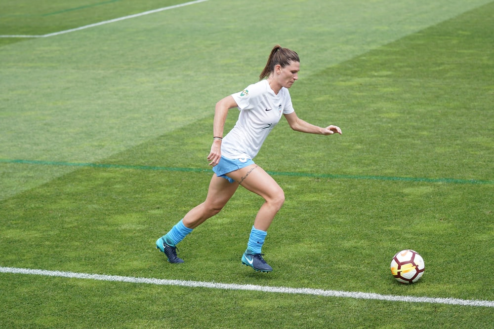 woman on football field dribbling soccer ball at daytime