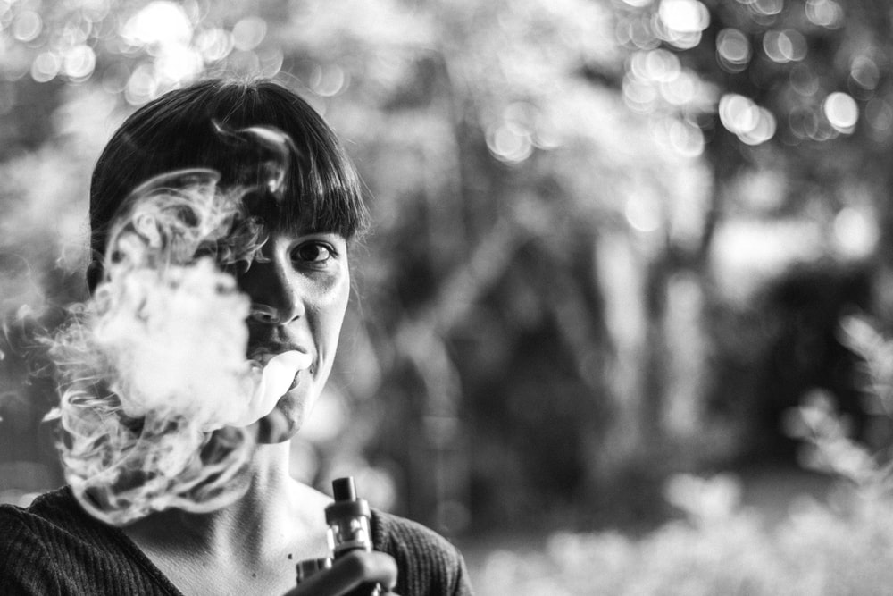grayscale photo of woman vaping