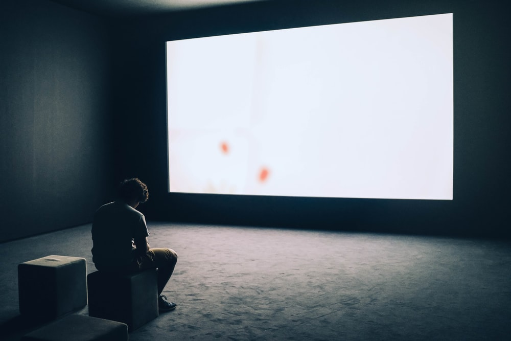 man sit in front projector screen