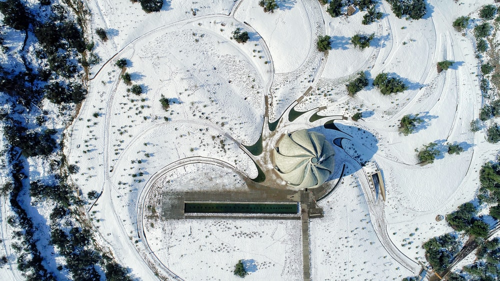 aerial photography of grey concrete structure surrounded by trees at daytime