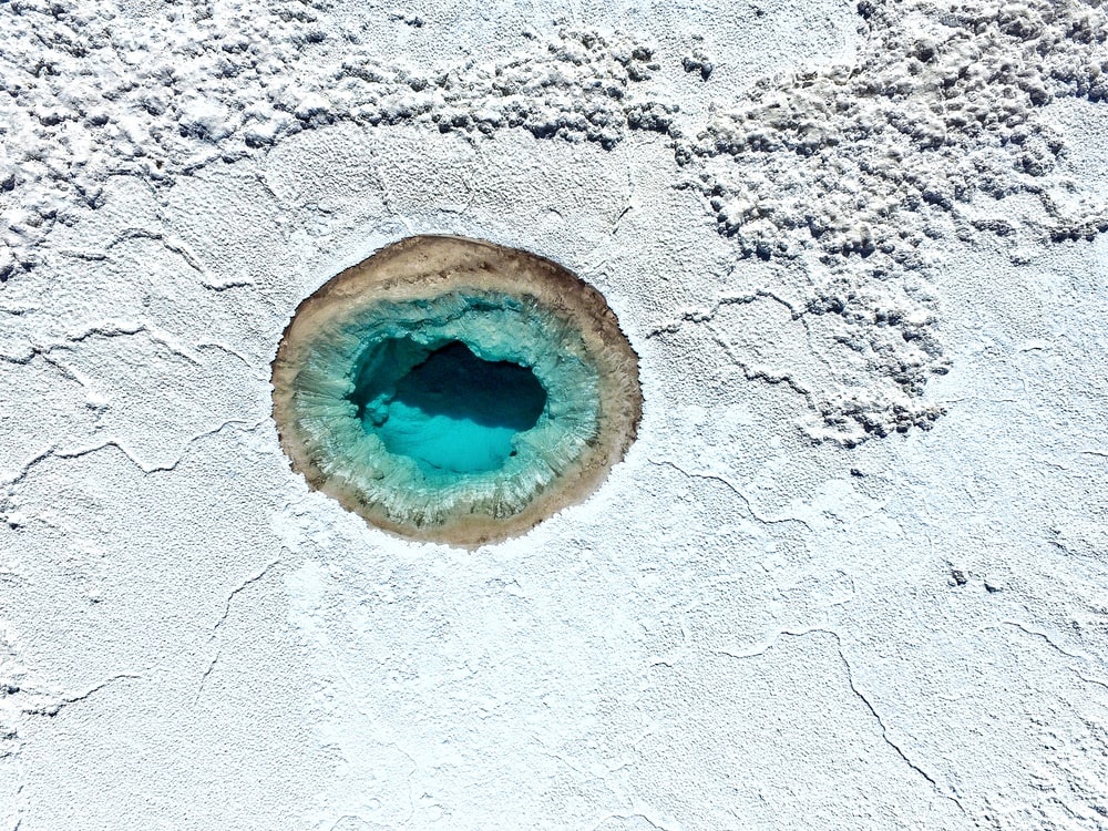a blue geyser surrounded by white rocks