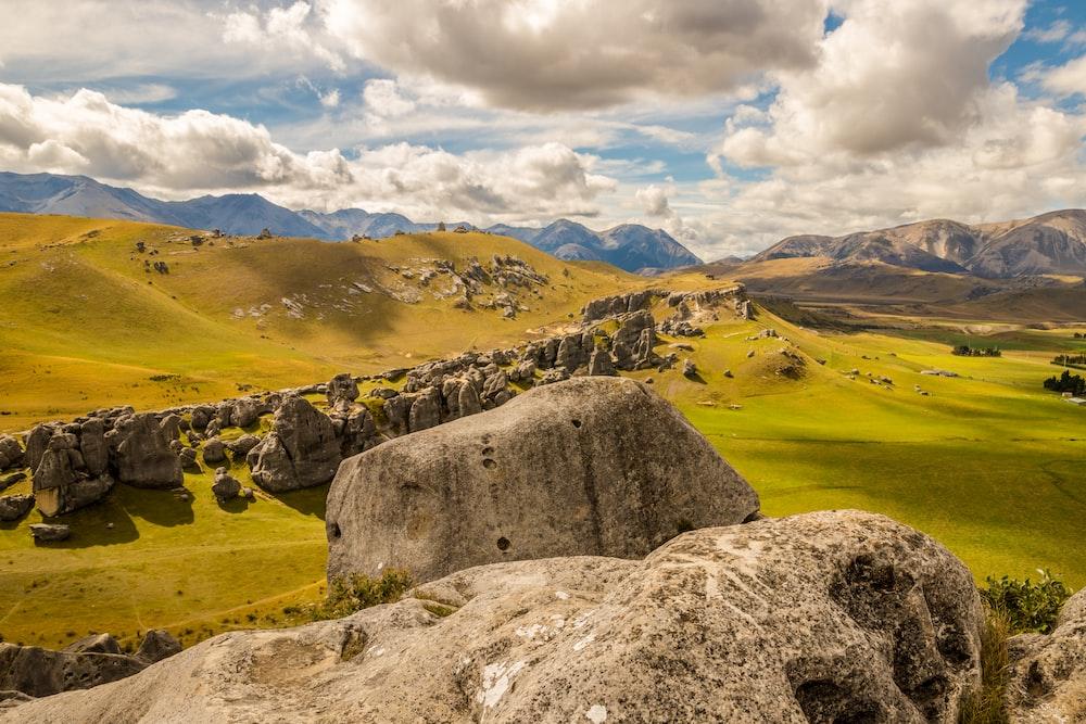 landscape photo of rocks on green grass field