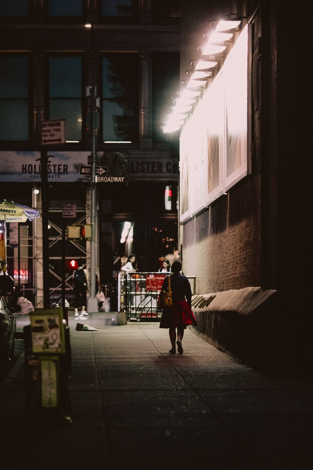 woman in black and red dress walking beside brown building