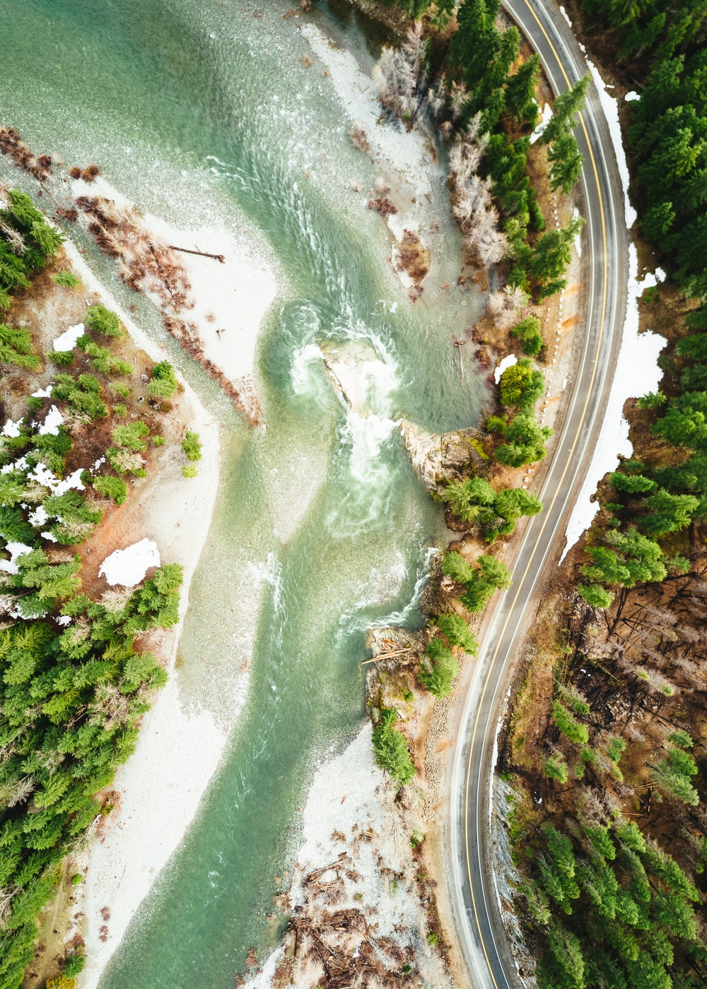 aerial photography of empty blacktop road at side of hill near river during daytime