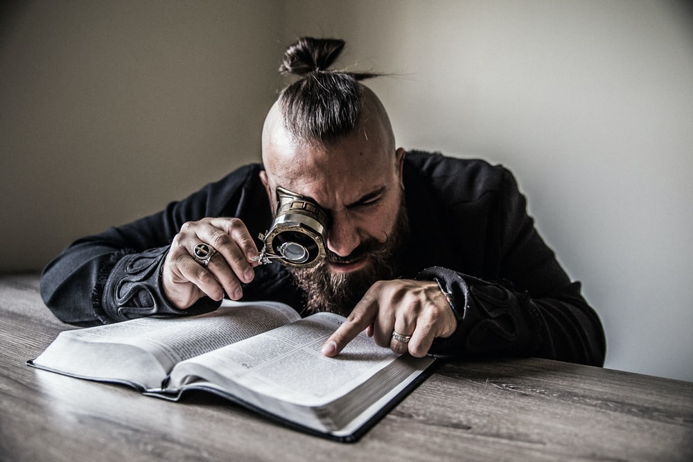 man holding reading magnifying glass rearing a book on brown wooden table
