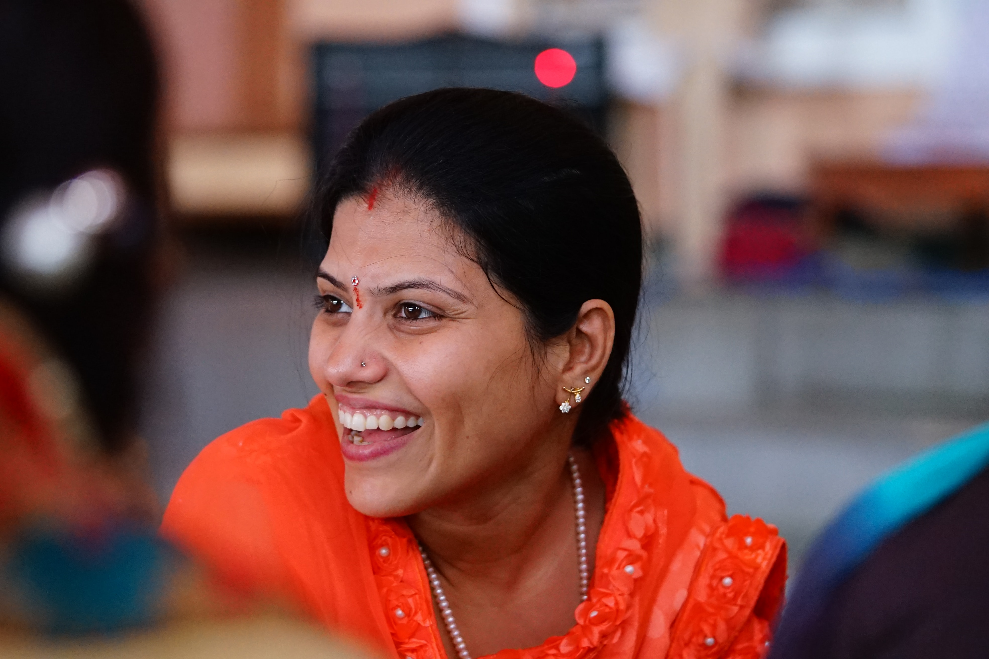 selective focus photography of smiling woman wearing red shirt