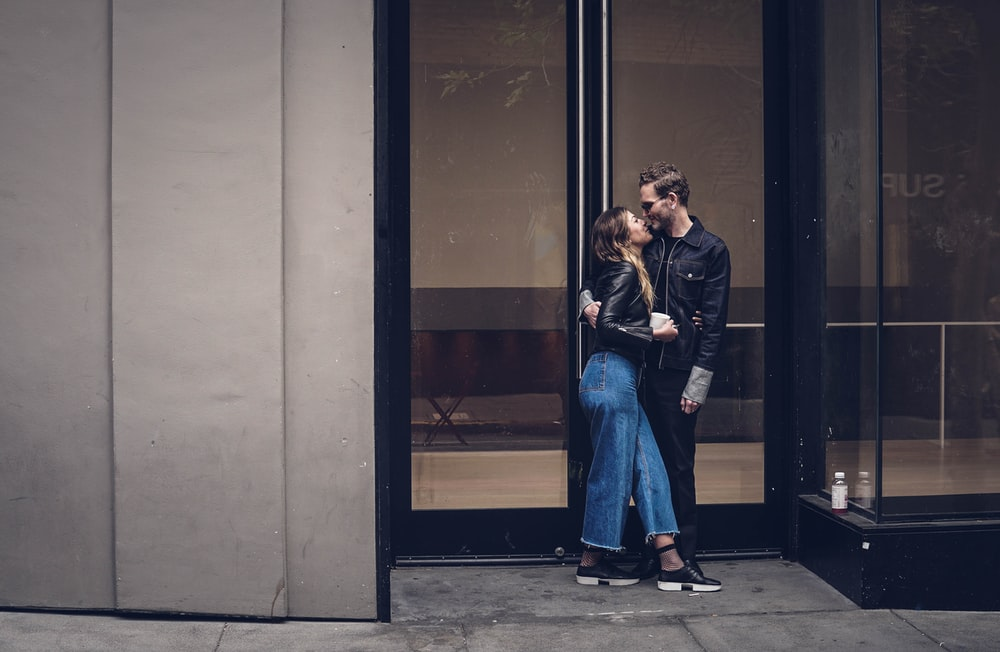 photo of man and woman kissing beside glass doors