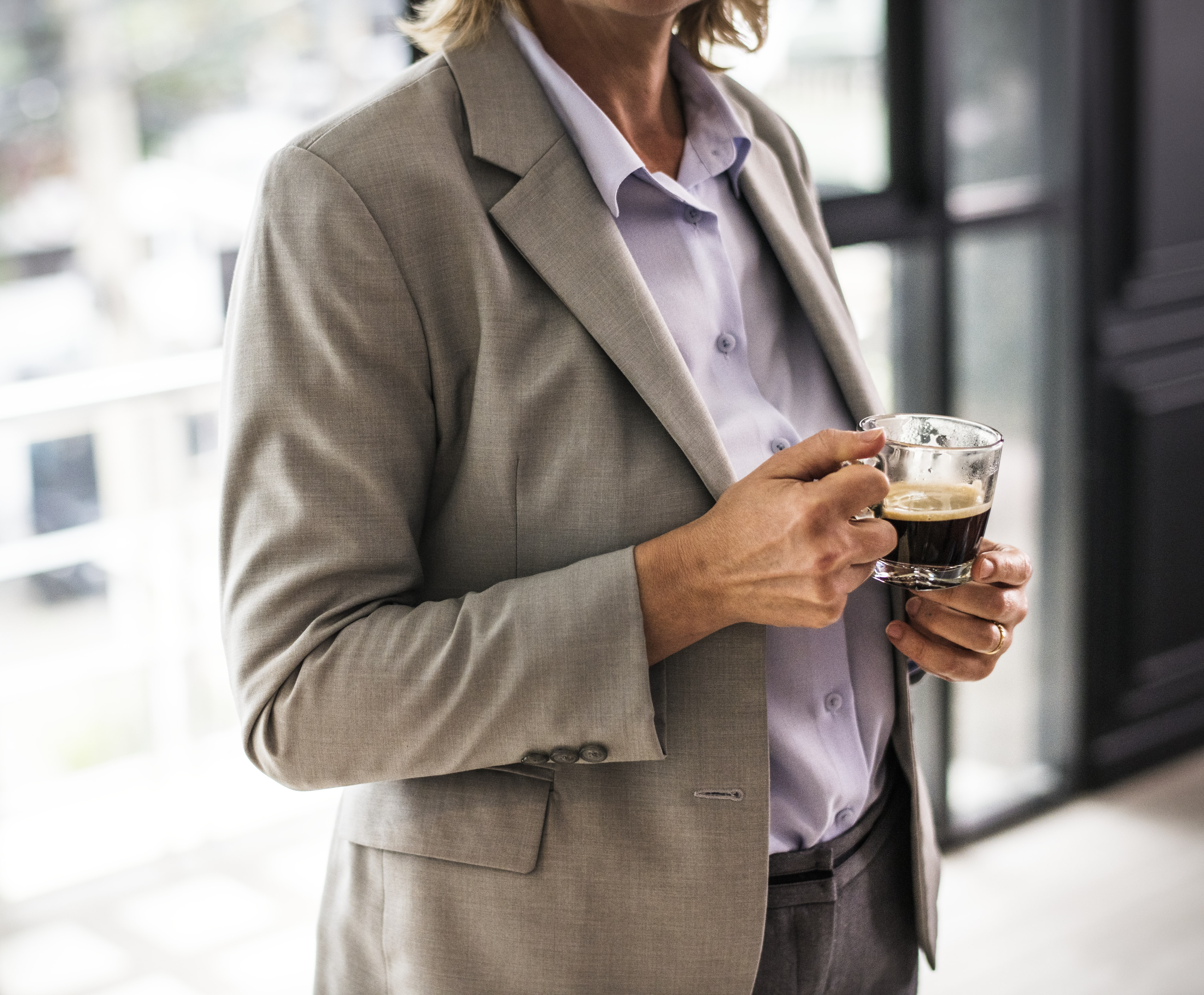 person wearing brown suit jacket holding cup of coffee