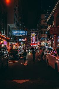 three person walk beside cars