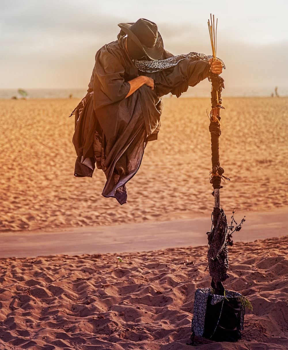 person in overall suit holding rod floating on desert field