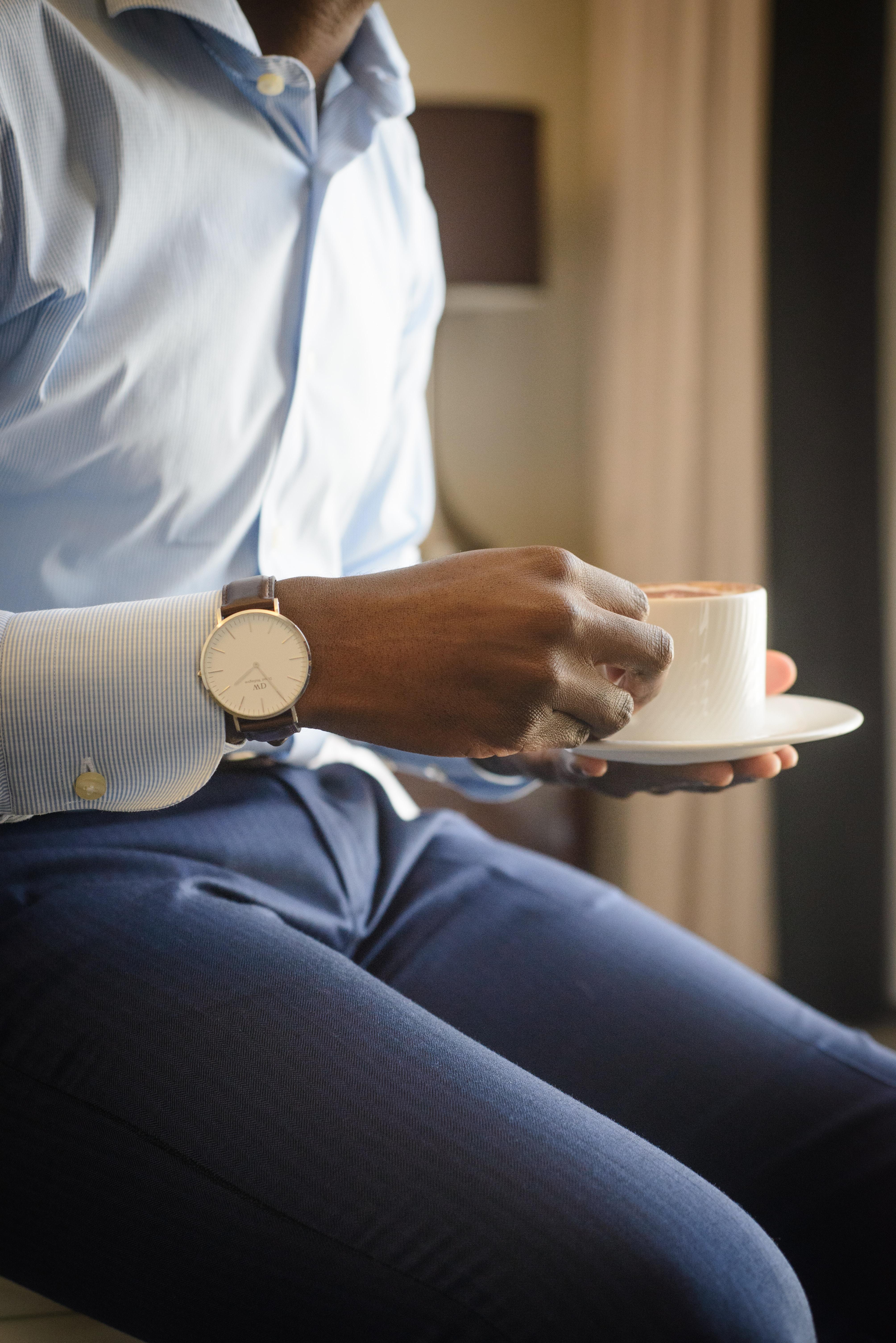 man holding teacup and saucer