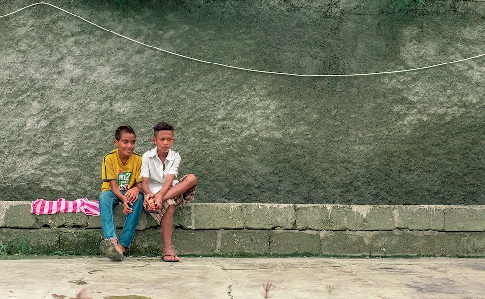 two boy sitting on gray pavement