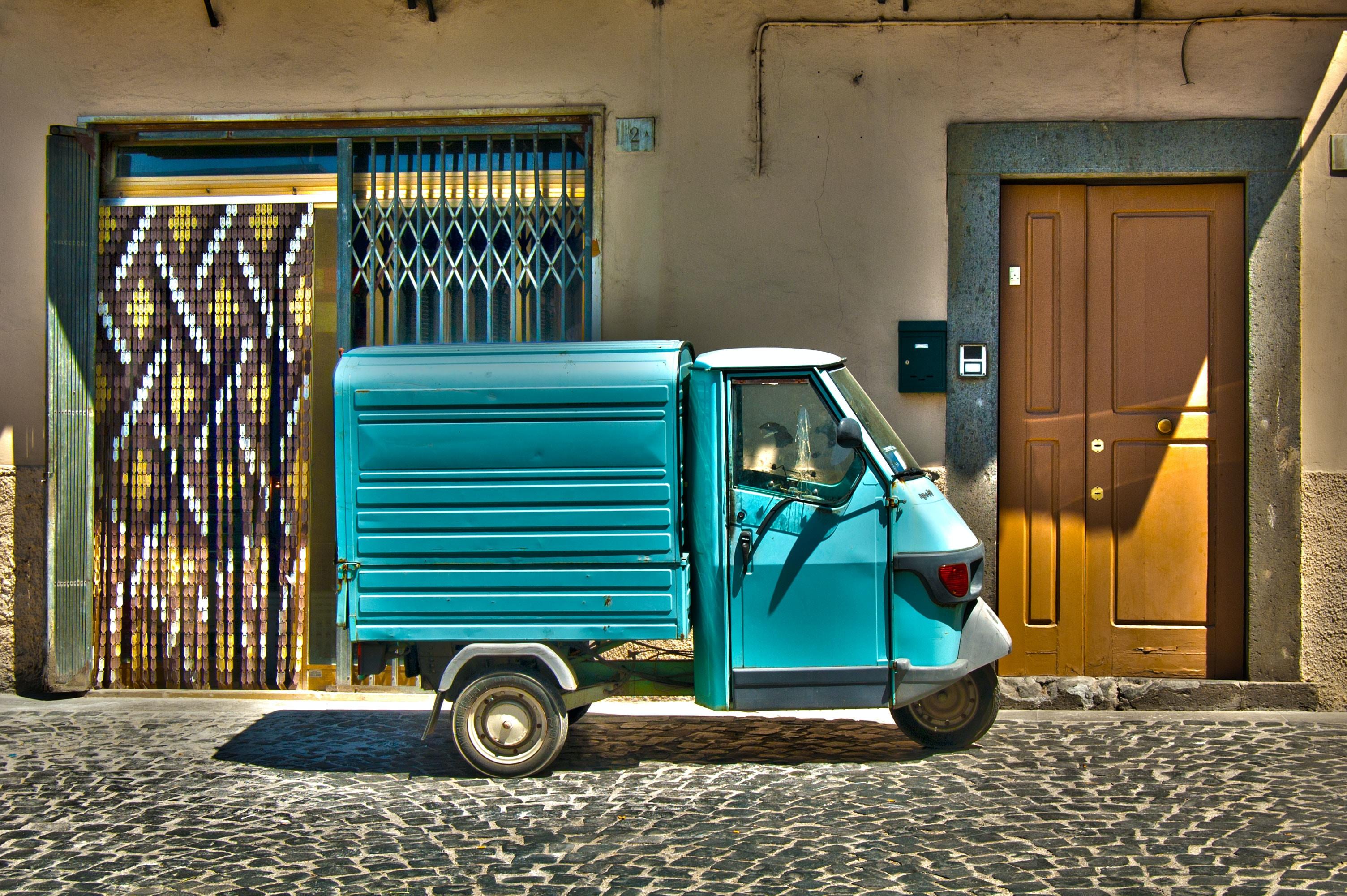 person taking photo of blue auto rickshaw park near concrete house