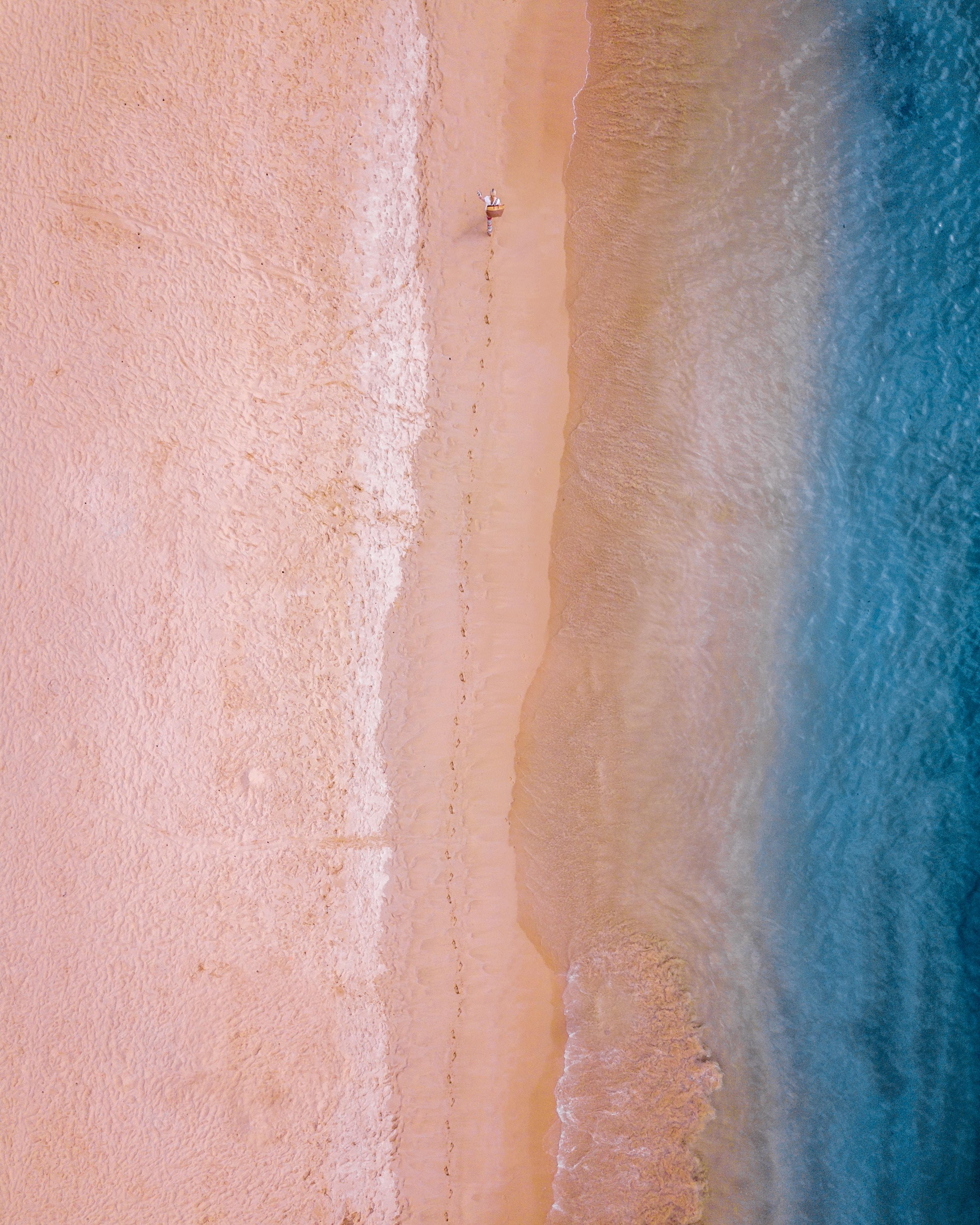 person walking on sand near seashore leaving foot trails