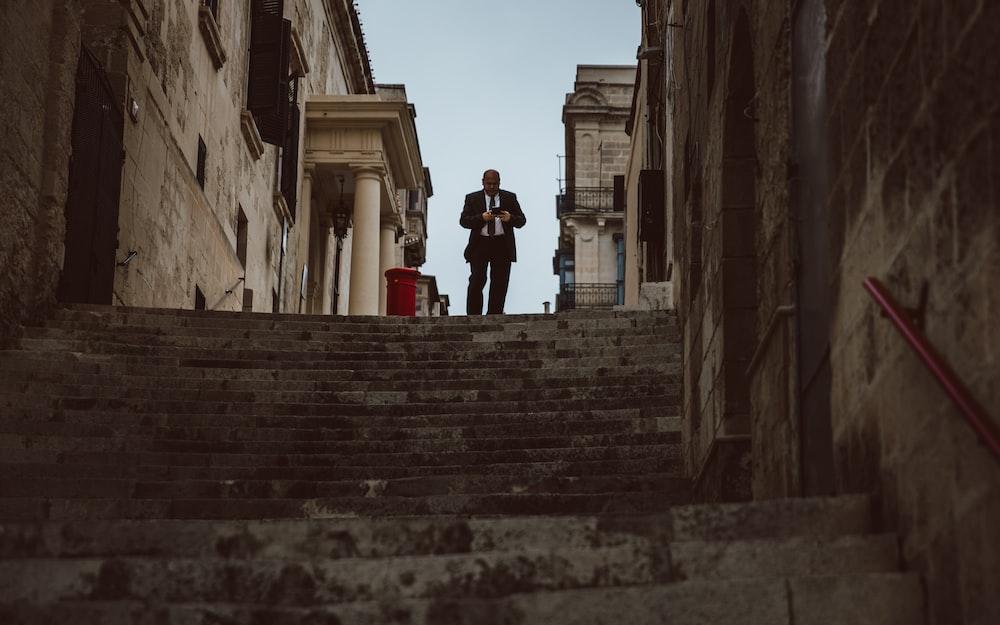 man walking downstairs between concrete buildings