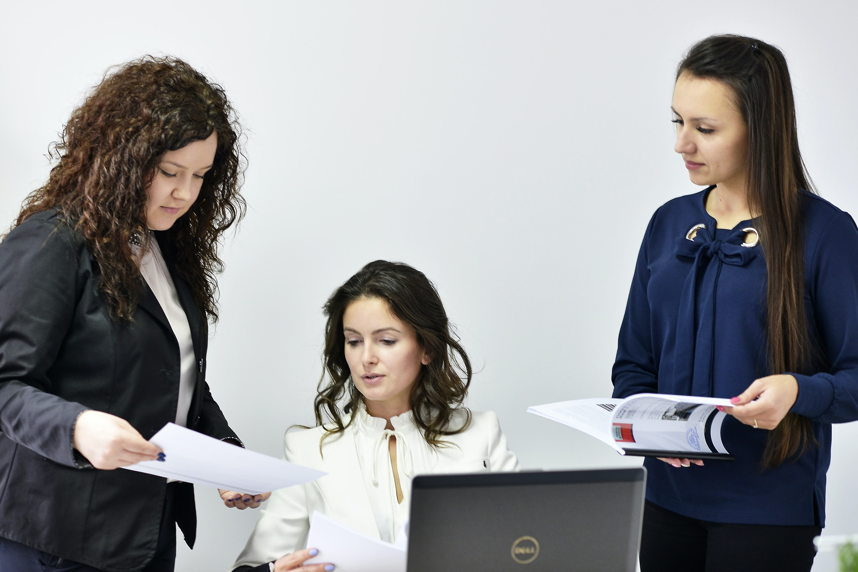 woman in black top showing papers to woman in white shirt near Dell laptop