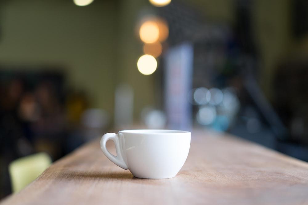 bokeh photography of white mug on brown table
