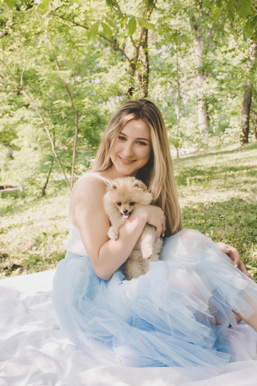 woman sitting on white picnic mat while holding dog