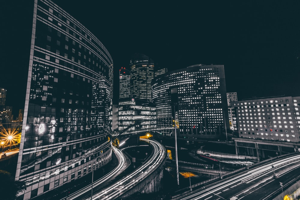 time lapse photography of vehicle passing on road near buildings