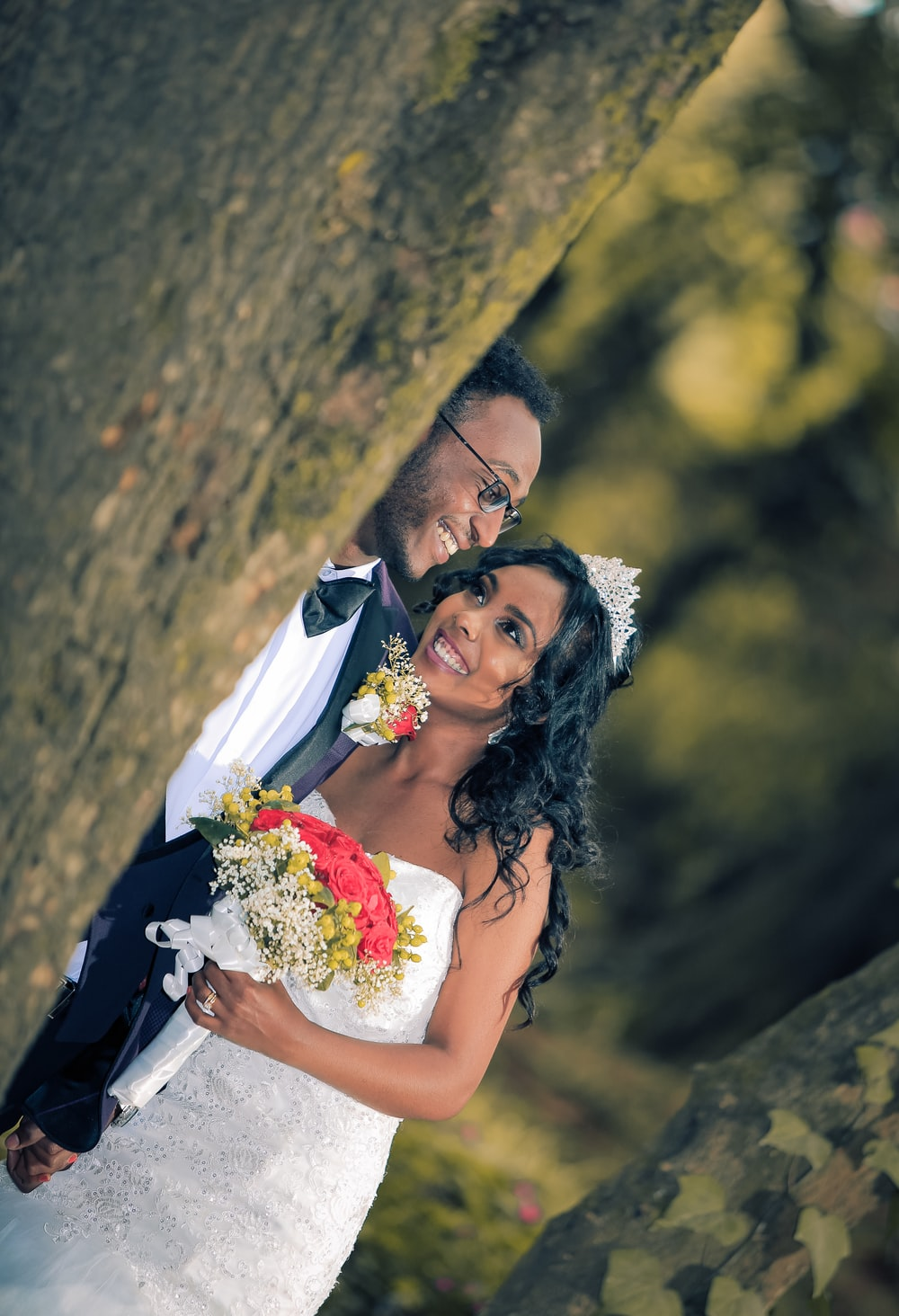 photo of couple wearing suit jacket and wedding gown
