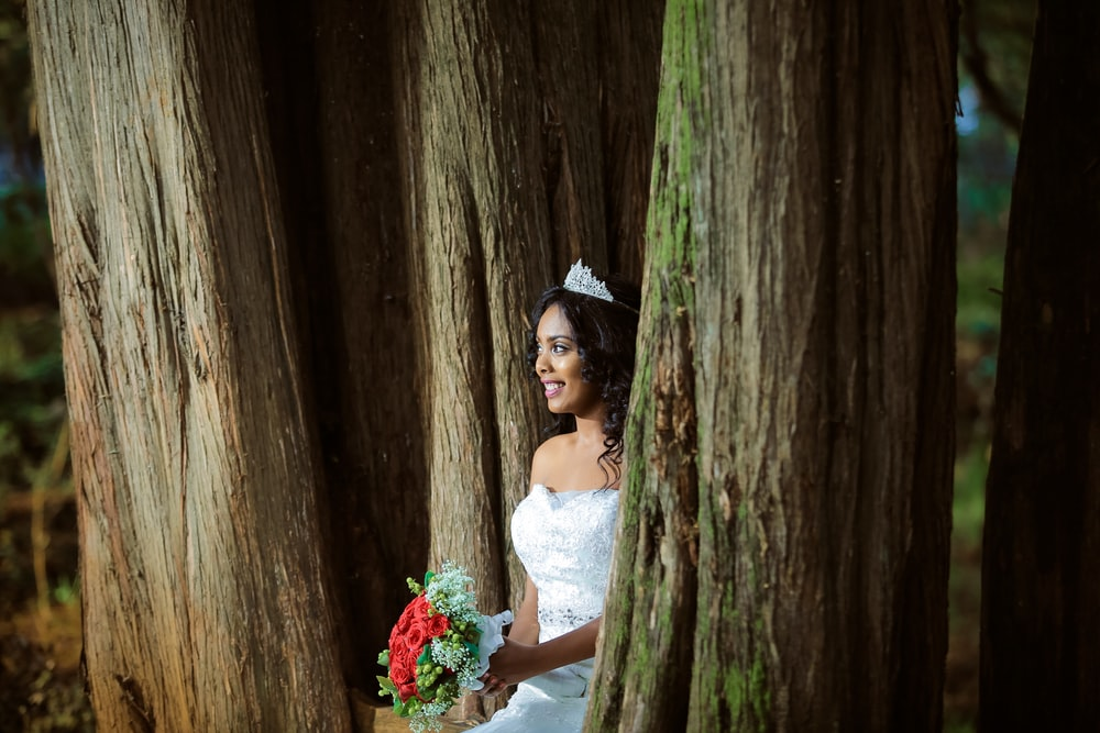 woman wearing wedding gown standing holding bouquet between trees