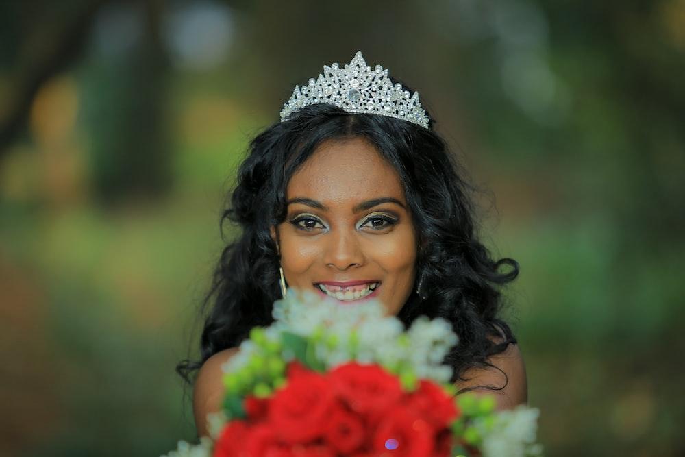 woman wearing tiara holding flower bouquet