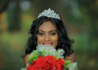 woman wearing tiara holding flower bouquet