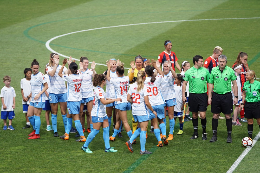 female soccer team standing on field with officials and children