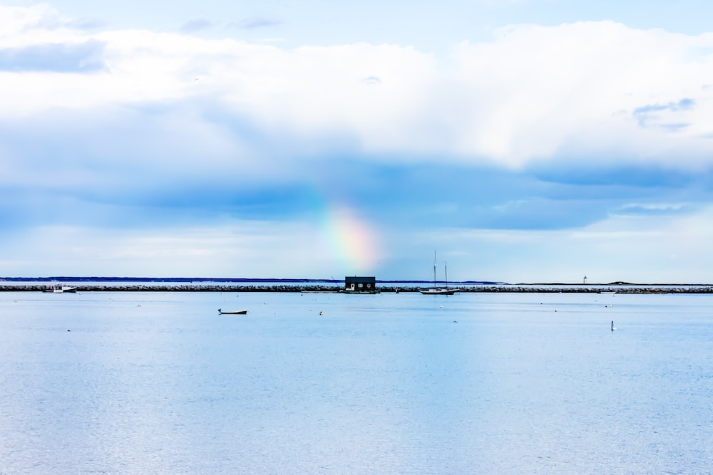 aerial view photography of body of water under cloudy sky with rainbow