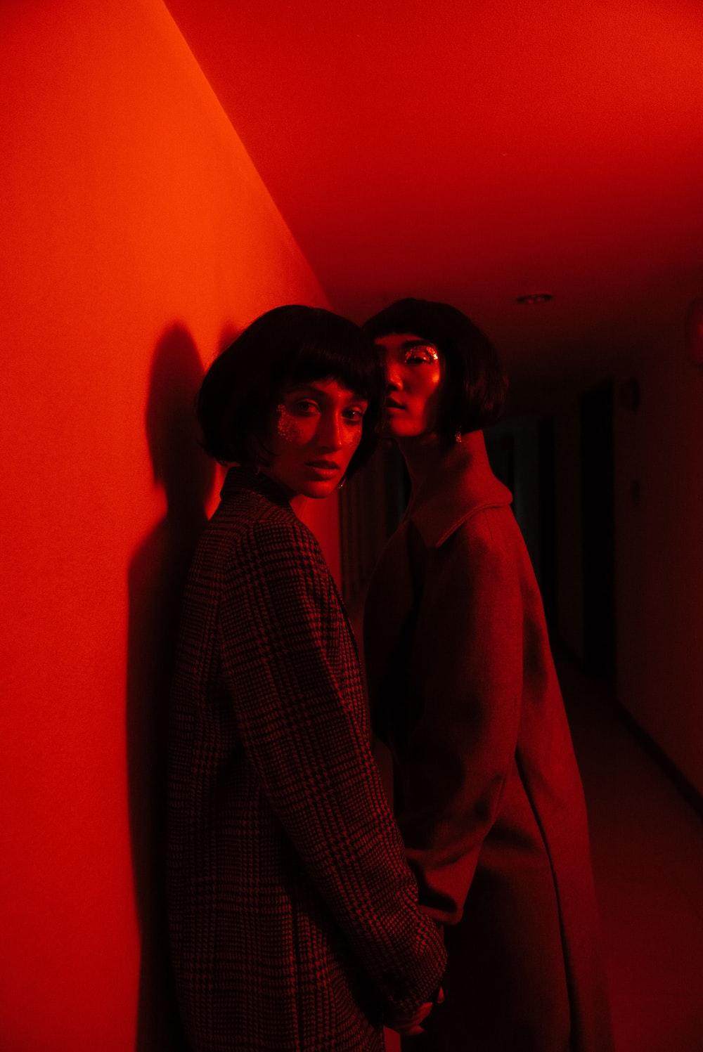 two woman wearing coat standing near wall