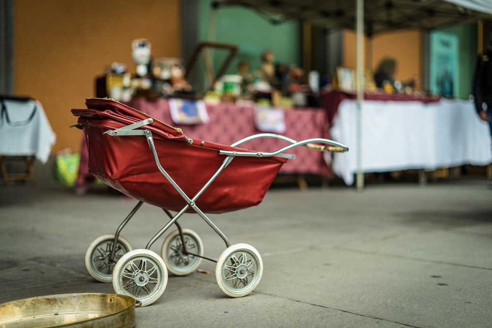 selective focus photography of red bassinet stroller