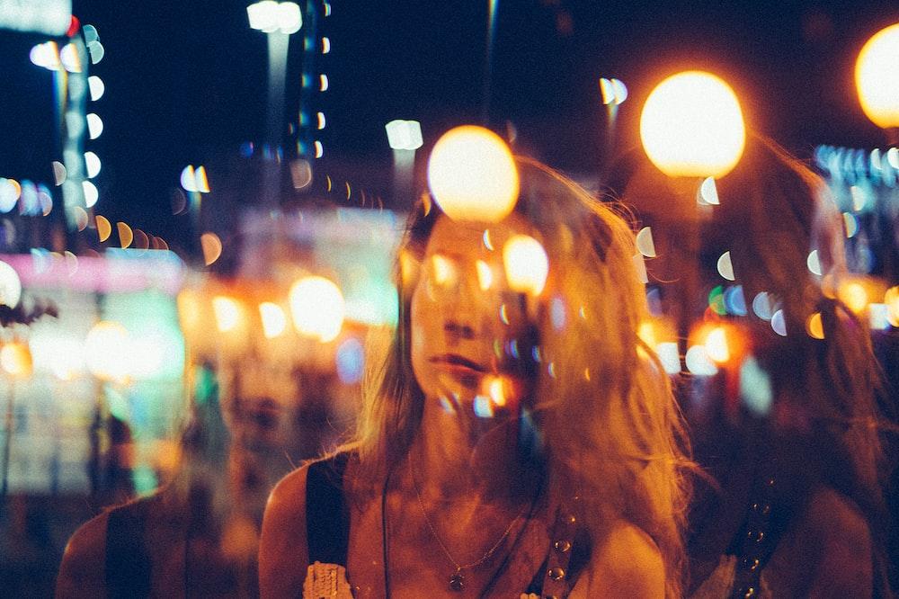 bokeh photo of woman standing near sea at night time