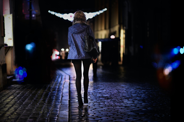 woman walking on street during night