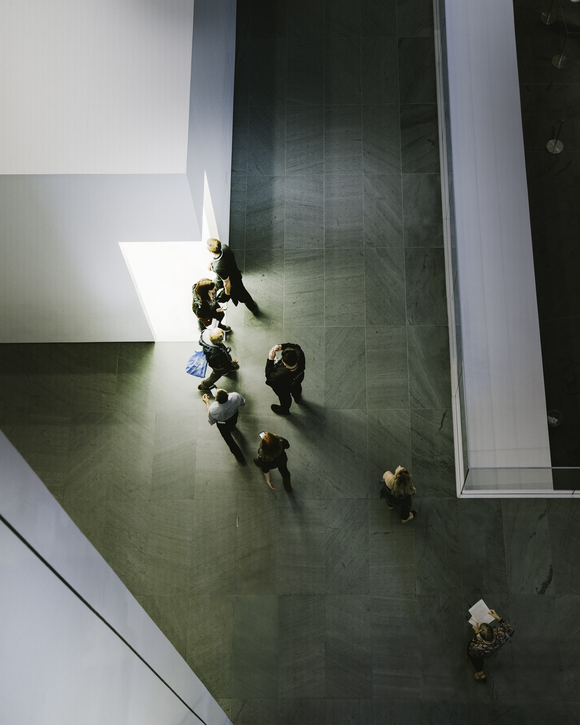 aerial photography of people standing and walking in front on white concrete building