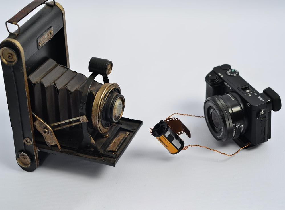 black folding camera and black MILC camera on white surface