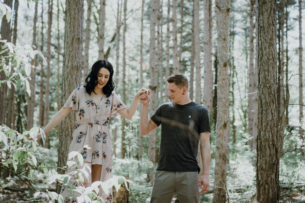 man holding hands with woman near trees