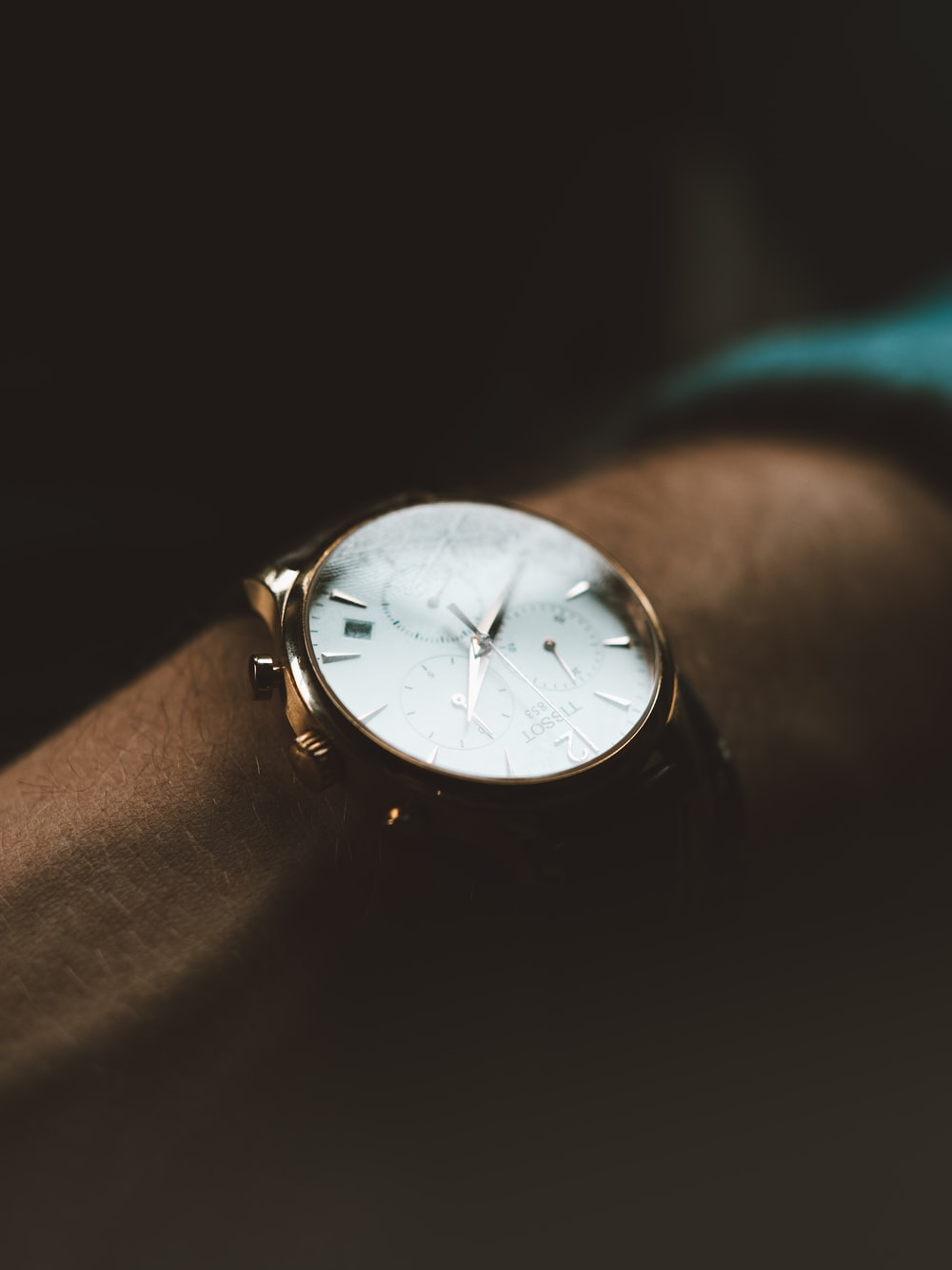 person wearing white chronograph watch
