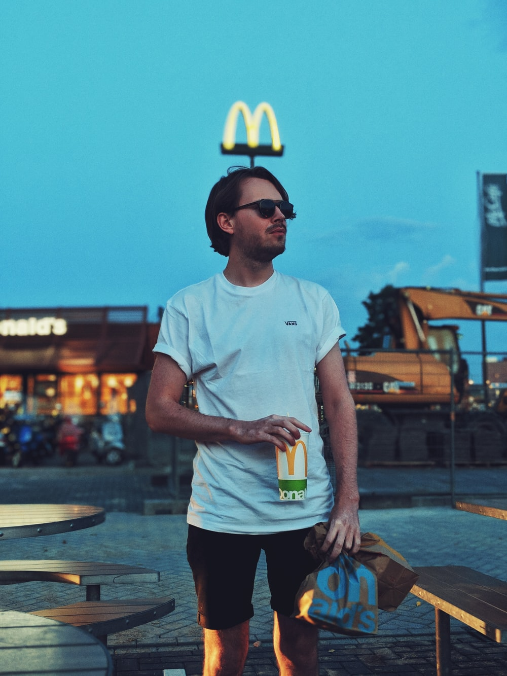 man holding McDonald cup beside camping table