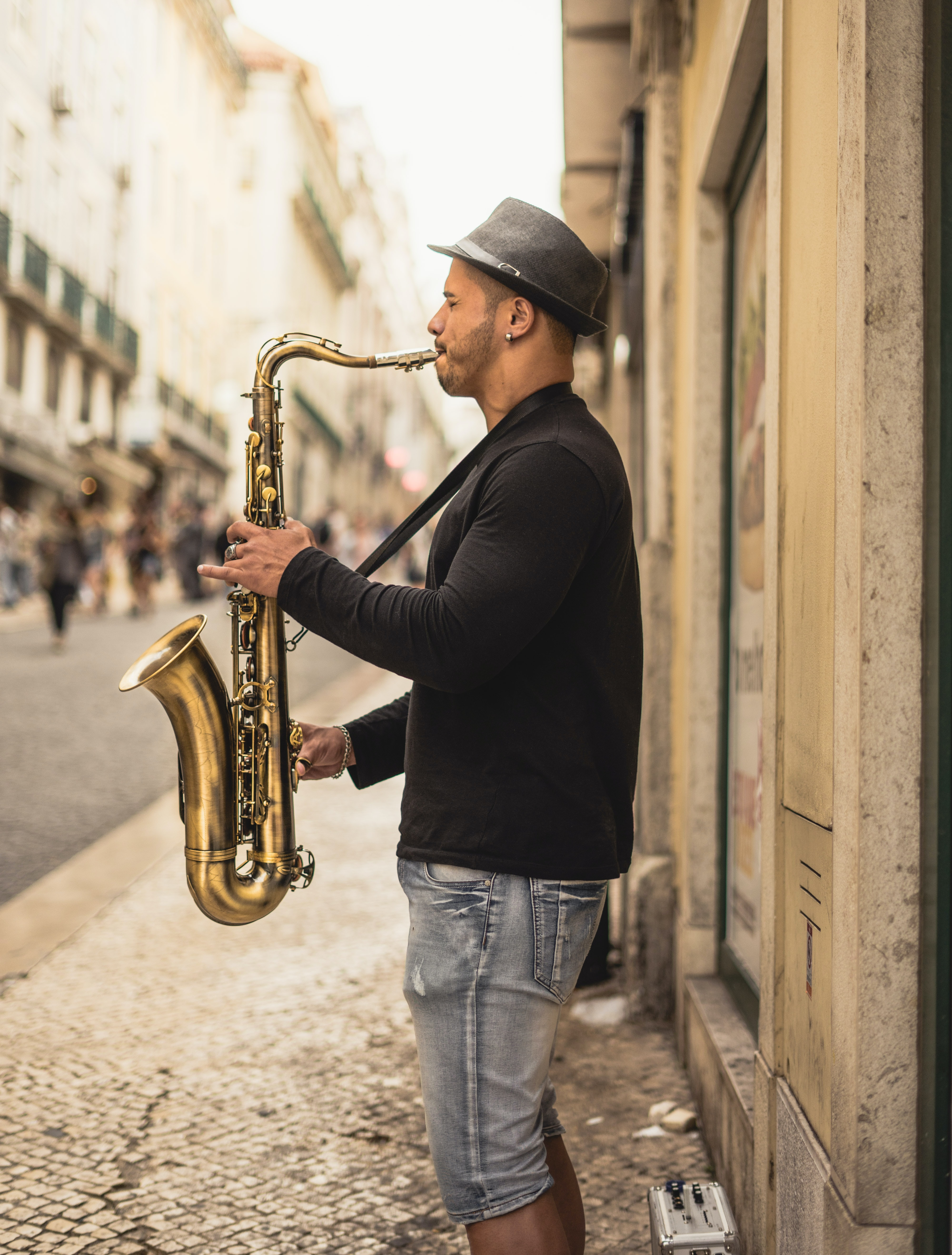 man playing copper-colored saxophone on street during daytime