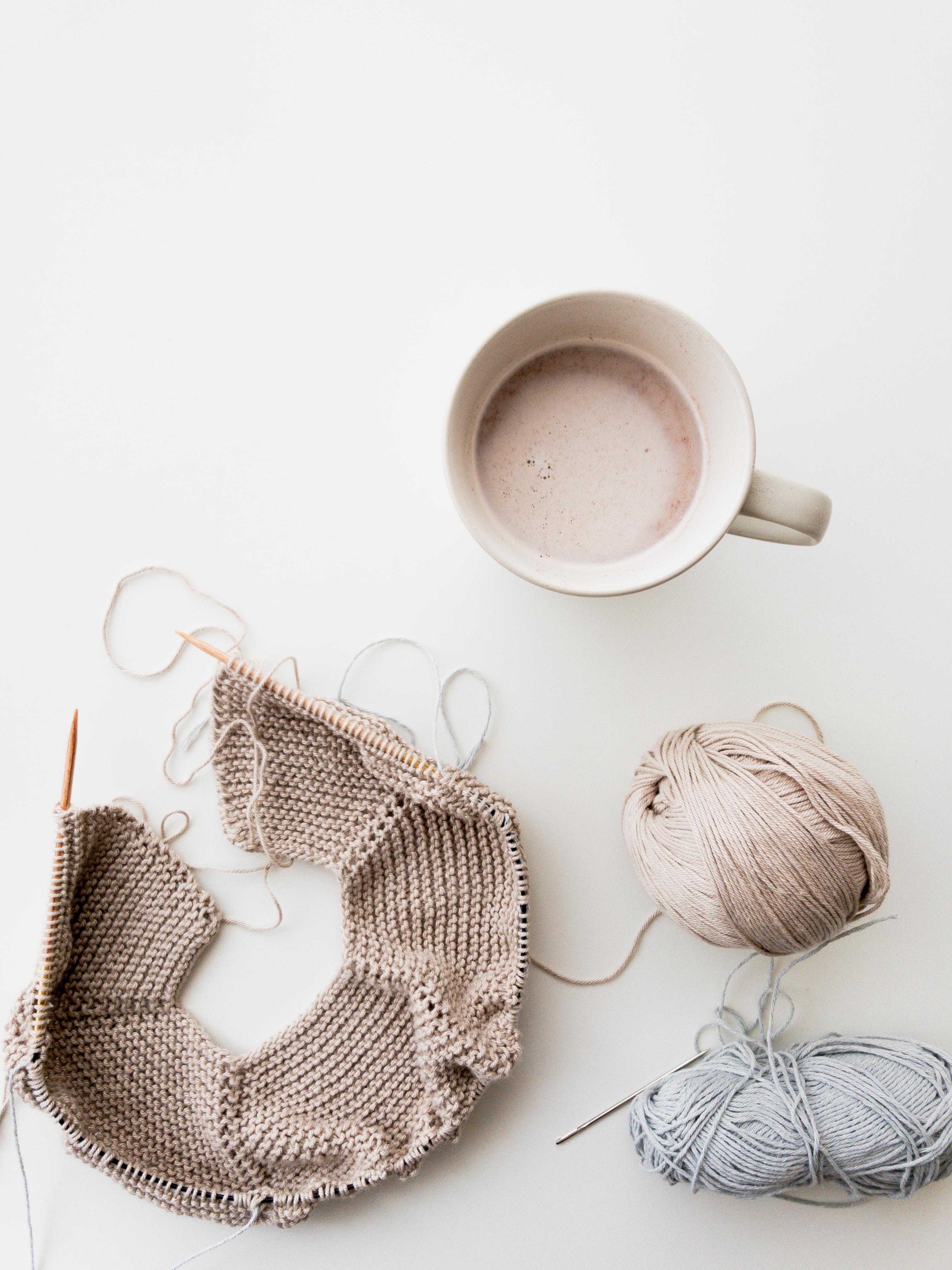 gray and blue yarns beside mug
