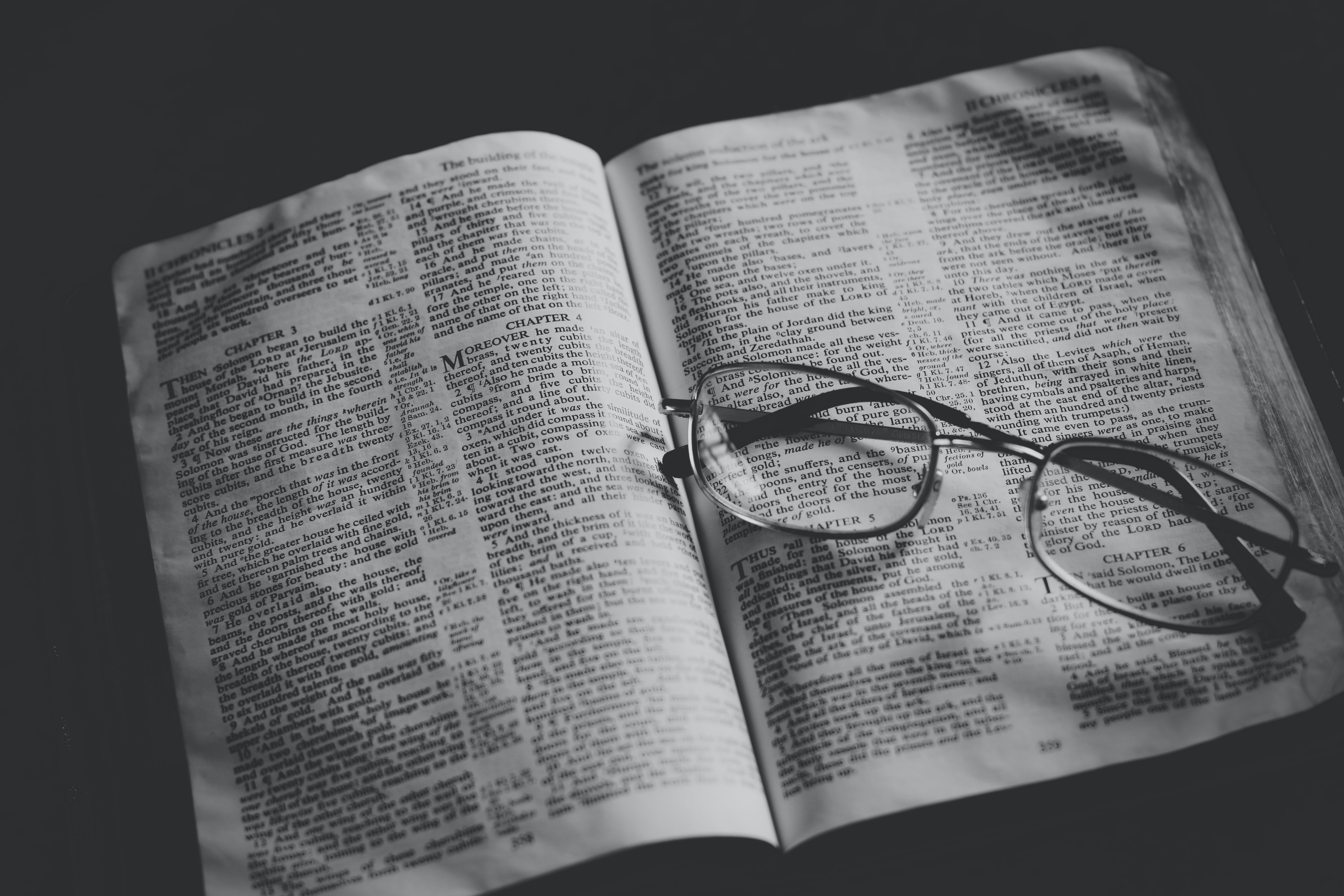 grayscale photo of eyeglasses on top of book