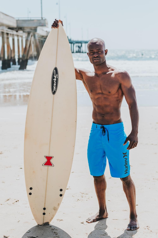 man standing beside white surfboard