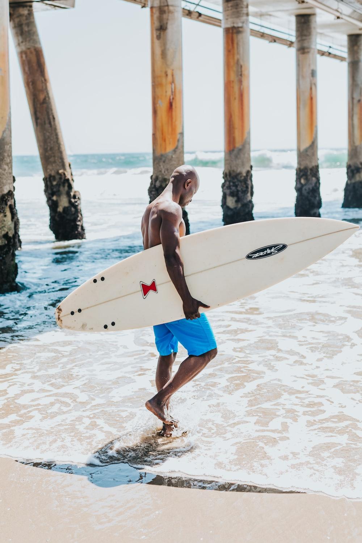 man holding white surfboard walking across ocean